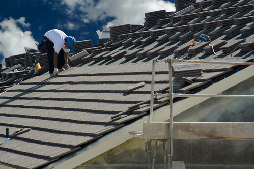 Roofer Laying Tile Shingles on a New Home